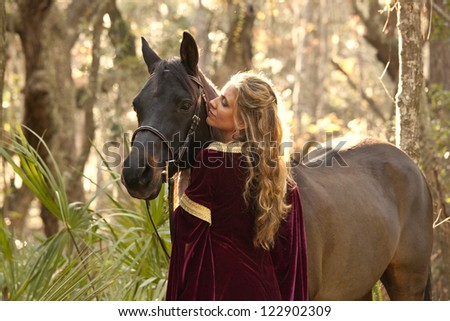 woman with medieval dress in forest with horse - stock photo