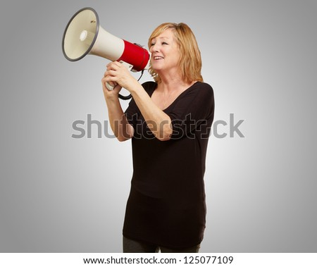 Woman with megaphone isolated on gray background - stock photo
