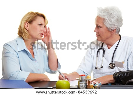 Woman with migraine at an elderly doctor - stock photo