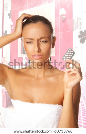 Woman with Migraine Headache holding pills on one hand - stock photo