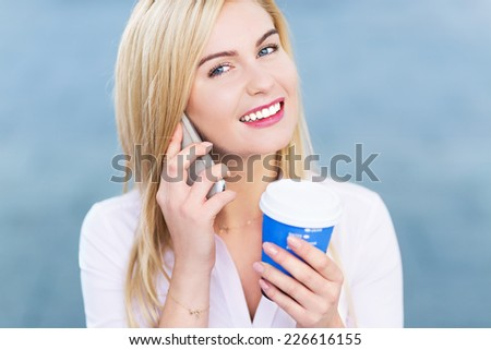 Woman with mobile phone and coffee to go