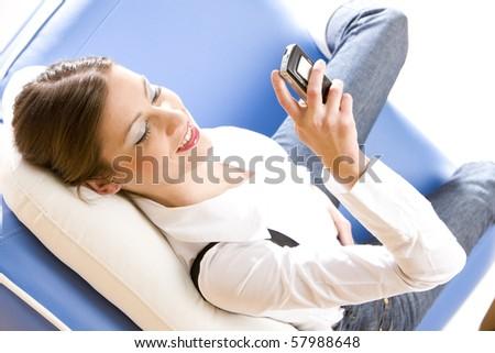 woman with mobile phone lying on sofa - stock photo