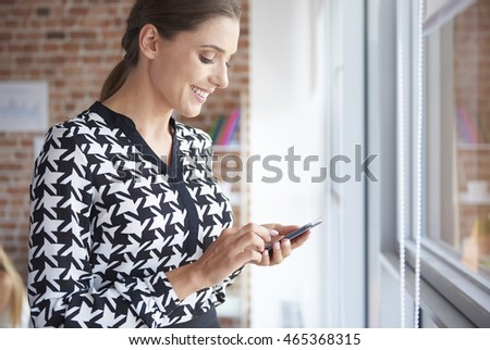 Woman with mobile phone next to the window