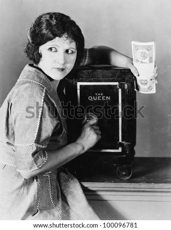 Woman with money and safe - stock photo