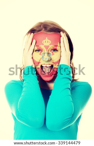 Woman with Montenegro flag painted on face. - stock photo