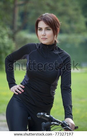 woman with mountain bike is having a break - stock photo