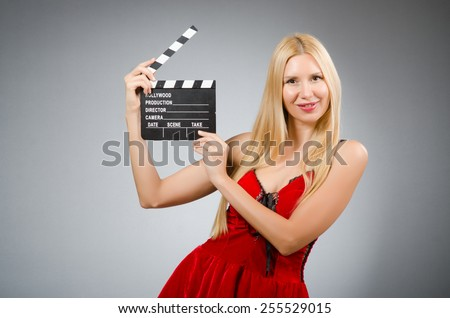 Woman with movie board wearing red dress - stock photo