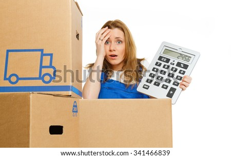 Woman with moving boxes with big calculator - stock photo