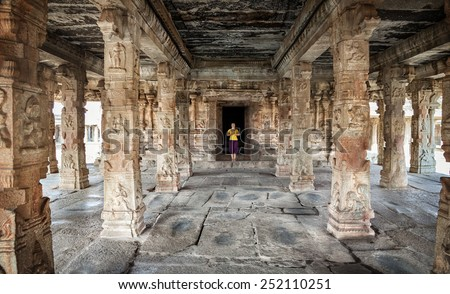 Woman with Namaste mudra standing in ancient temple with carving columns in Hampi, Karnataka, India - stock photo