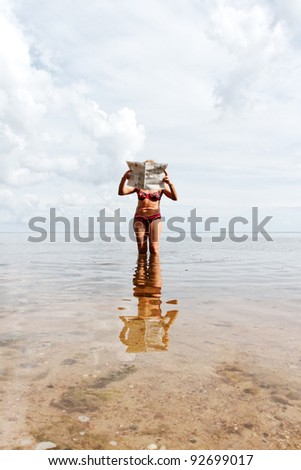 Woman with newspaper on the beach. - stock photo