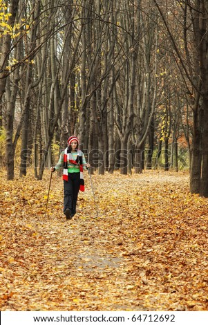 woman with Nordic walking sticks in autumn forest alley with selective focus