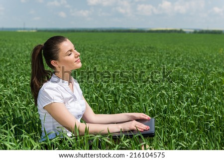 woman with notebook in the green field