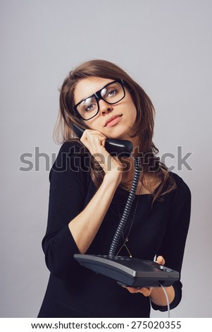 Woman with office or home phone. On a gray background.