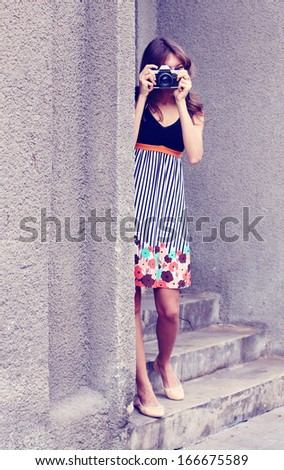 woman with old camera outdoors - stock photo