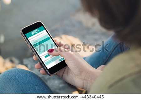 woman with online customer satisfaction survey on her phone. All screen graphics are made up. - stock photo
