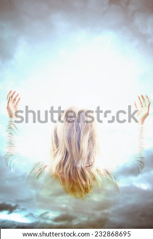 woman with open arms in front of a divine light in the sky - stock photo