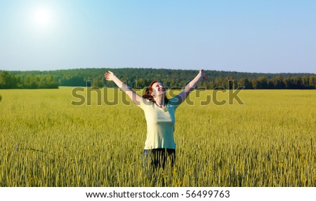 woman with open arms in the green cereal field.