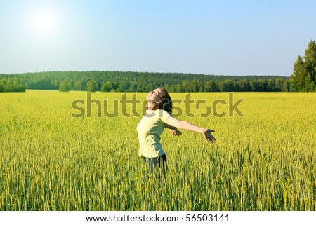 woman with open arms in the green cereal field. - stock photo