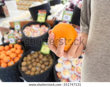 Woman with orange choosing fruit at street market - stock photo