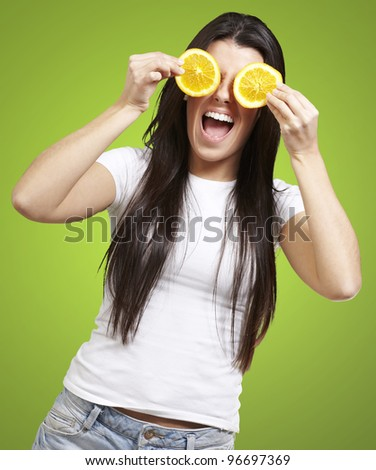 woman with orange slices as eyes against a green background - stock photo