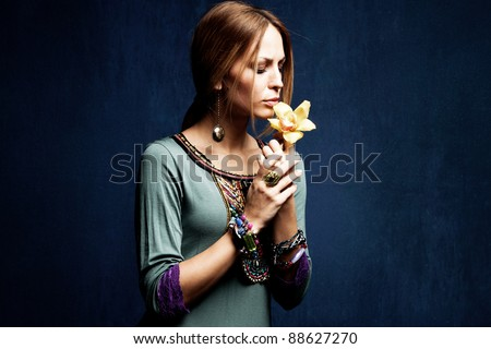 woman with orchid in hands, studio shot - stock photo