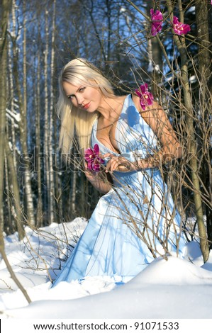 Woman with orchid in the winter forest. She is dressed only in silk gown