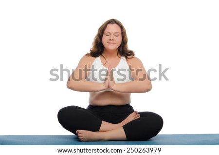 woman with overweight is meditating on blue mat