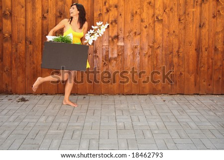 Woman with packed cardboard box going at the wall with flower - stock photo