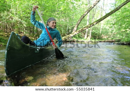 woman with paddle in a canoe on the Küstrinchen Bach in Germany - stock photo