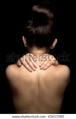 Woman with pain in her neck and shoulder, Isolated medical shot over black background. - stock photo