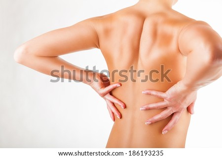 Woman with pain in the back on a white background - stock photo