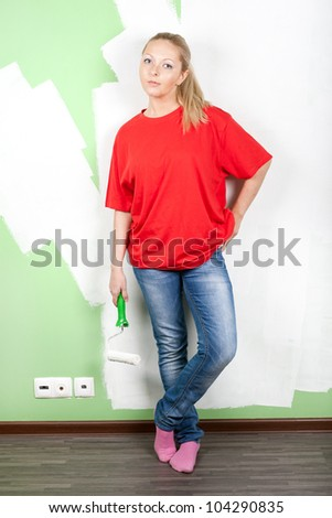 Woman with paint roller in hand standing near painting wall