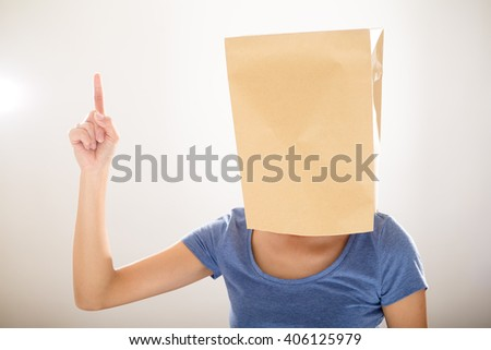 Woman with paper bag cover her head and finger point up - stock photo