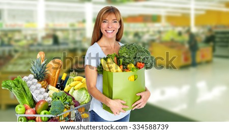 Woman with paper bag of vegetables over grocery store background. - stock photo