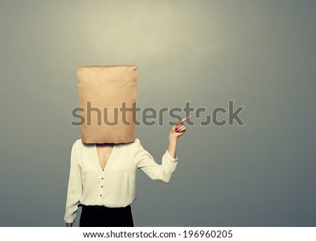 woman with paper bag on the head pointing over dark background - stock photo