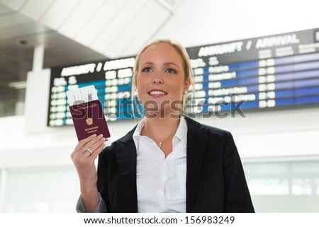 woman with passport and airline tickets at an airport waiting for her flight to the holiday. - stock photo