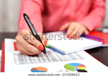woman with pen checks the financial report - stock photo