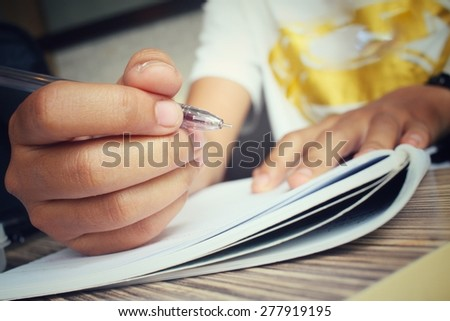 Woman with pen writing on paper - stock photo