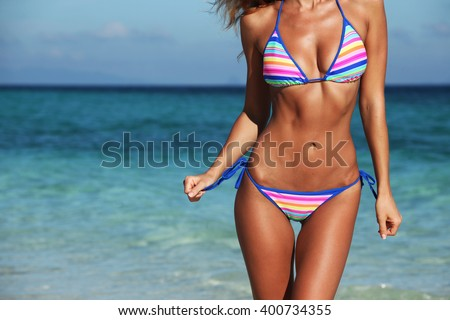 Woman with perfect body in bikini over blue sea background