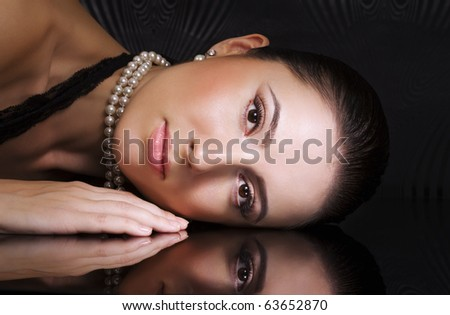Woman with perfect makeup on dark background
