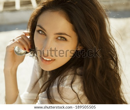 Woman with perfume. Smiling beautiful woman holding bottle of perfume and smelling aroma. horizontal shot - stock photo