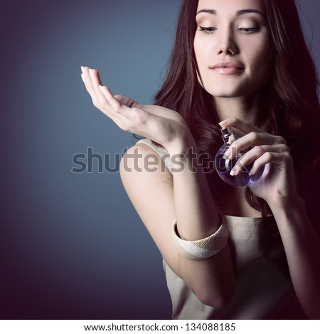 Woman with perfume, young beautiful girl holding bottle of perfume and smelling aroma, over blue purple background - stock photo