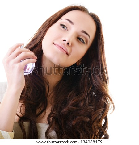 Woman with perfume, young beautiful girl holding bottle of perfume and smelling aroma, over white - stock photo