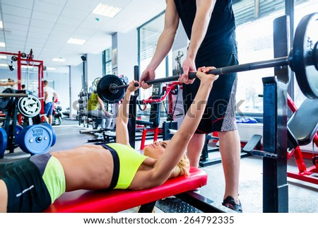 Woman with personal trainer at bench press in gym exercising for better fitness - stock photo