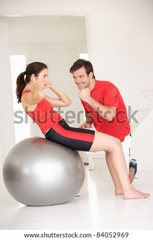 Woman with personal trainer in home gym - stock photo