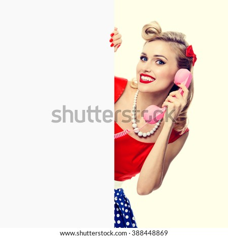 Woman with phone, in pin-up style dress, showing blank signboard with copyspace area. Caucasian blond model posing in retro fashion and vintage concept studio shoot. - stock photo