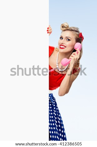 woman with phone, in pin-up style dress, showing blank signboard with copyspace area, on blue background. Caucasian blond model posing in retro fashion and vintage concept studio shoot. - stock photo