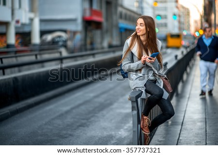 Woman with phone in the city - stock photo