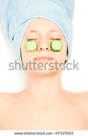 Woman with piece of cucumber on her face - stock photo