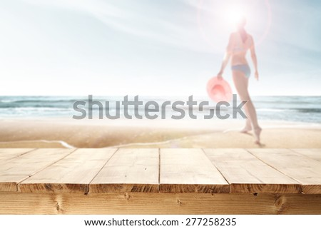 woman with pink hat on beach  and table of yellow wood